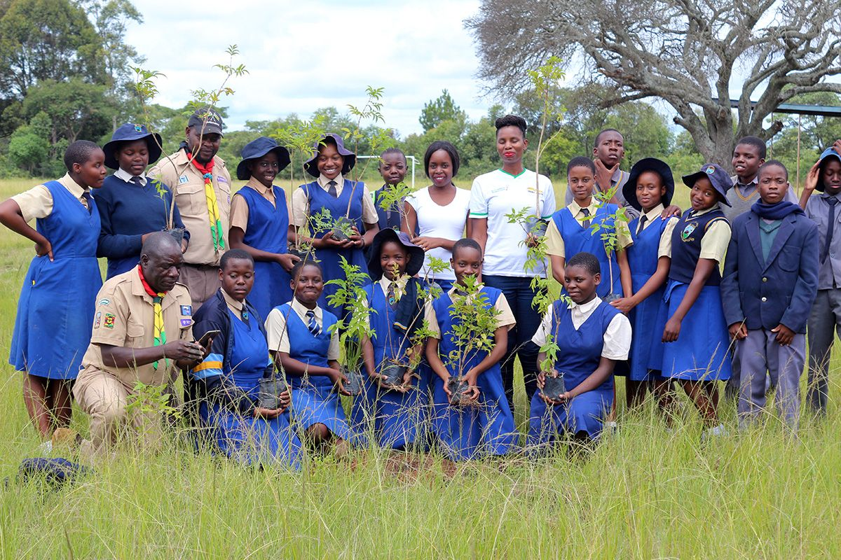 A group of children in blue school uniforms, with some adults, in a field with trees behind. Some are holding saplings.